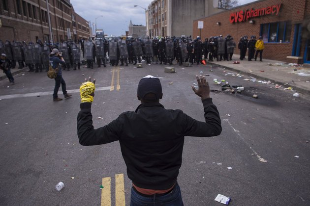 BALTIMORE, MD - APRIL 27: People stand with their hands up as officers move toward them near a CVS pharmacy near West North Avenue and Pennsylvania Avenue during a protest for Freddie Gray in Baltimore, MD on Monday April 27, 2015. Gray died from spinal injuries about a week after he was arrested and transported in a police van. (Photo by Jabin Botsford/The Washington Post via Getty Images)
